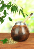 Calabash and bombilla with yerba mate on wooden table, on natural background — Stock Photo