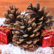 Christmas decoration with pine cones on wooden background — Stok fotoğraf #34173379