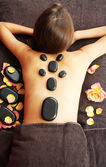 Beautiful young woman having stone massage in spa salon on color background — Stock Photo