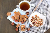 Many toffee in spoon and cup of tea on napkins on wooden table — Stock Photo