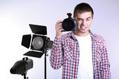 Handsome photographer with camera, on photo studio background — ストック写真