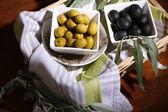 Oliven in schalen mit zweig auf serviette in korb auf holztisch — Stockfoto