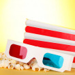 Popcorn and 3D glasses on yellow background — Stock Photo