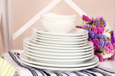 Stack of white plates on white shelf, on color wall background, close-up — Stock Photo
