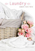 Rumpled bedding sheets in wicker basket isolated on white — Stock Photo