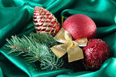 Beautiful Christmas decor on green satin cloth — Stock Photo