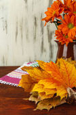 Beautiful autumn leaves with flowers on table on wooden background — Stock Photo
