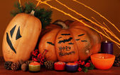 Composition for Halloween with pumpkins and candles on orange background — Stock Photo