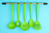 Plastic kitchen utensils on silver hooks on blue background — Stock Photo