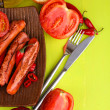 Delicious sausages with vegetables on plate on wooden table close-up — Stock Photo #34420101