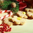 Cookies on ribbons with Christmas decorations on wooden table — Stock Photo #34422759