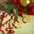 Cookies on ribbons with Christmas decorations on wooden table — Stock Photo #34425375