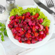 Beet salad on plate on napkin on wooden board isolated on white — Stock Photo #34426541