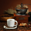 Cup of coffee, grinder, turk and coffee beans on brown background — Stock fotografie