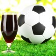 Glass of beer on lawn with ball — Stock Photo #34427585
