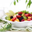 Fruit salad in plate on wooden table on bright background — Stock Photo
