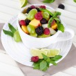 Stock Photo: Fruit salad in cup on wooden table