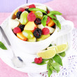 Fruit salad in cup on napkin on wooden table — Stock Photo