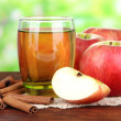 Ripe apples with with cinnamon sticks and glass of  apple drink  on  wooden table, on bright background — 图库照片