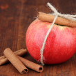Ripe apples with with cinnamon sticks on wooden background — Stock Photo
