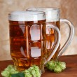 Stock Photo: Glasses of beer and hops, on wooden table