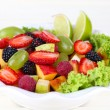 Fruit salad in plate isolated on white — Stock Photo