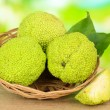 Osage Orange fruits (Maclurpomifera) in basket, on wooden table, on nature background — Stock Photo #34428465