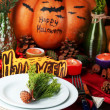 Table setting for Halloween with pumpkin and candles close-up — Stock Photo #34428663