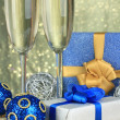 Glasses of champagne with gift boxes on shiny background — Stock Photo
