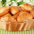Tasty croissants in wicker basket on table on white background — Stock Photo #34428747
