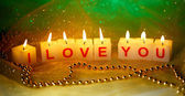 Candles with printed sign I LOVE YOU,on blur lights background — Stock Photo