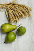 Pears and sheaf on wooden background — Stock Photo