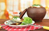 Aardappelpannenkoekjes in pot, op houten tafel, op lichte achtergrond — Stockfoto