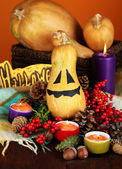 Composition for Halloween with pumpkins and candles on color background — Stock Photo
