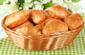Tasty croissants in wicker basket on table on white background — Stock Photo