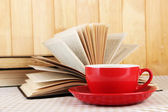 Cup of coffee and books on tablecloth on wooden background — Stock Photo