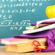 Purple backpack with school supplies on wooden table on green desk background — Stock Photo #34431953