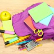 Purple backpack with school supplies on wooden background — Stock Photo #34432215