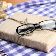 Stock Photo: Composition with old book, eye glasses, and plaid on wooden background