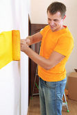Young man paints wall in new flat — Stock Photo