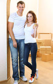 Young couple with keys to your new home on room background — Foto de Stock