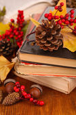 Books and autumn leaves on wooden table close-up — Stock Photo
