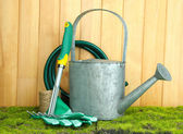 Gardening tools on grass on wooden background — Stock Photo