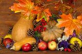 Composição de outono de maçãs, abóboras, flores e ramos secos na mesa de madeira com fundo de madeira — Fotografia Stock