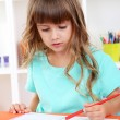 Little girl draws sitting at table in room on shelves background — Stock Photo #34493569