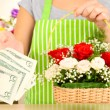 Florist makes flowers bouquet in wicker basket — Stock Photo #34496081
