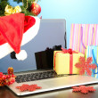 Laptop with gifts on table on blue background — Stock Photo