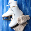 Wool fingerless gloves and skates for figure skating, on wooden background — Foto Stock