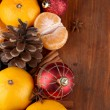 Christmas tangerines and Christmas toys on wooden table close-up — Lizenzfreies Foto