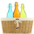 Color glass bottles in wicker basket, isolated on white — Stock Photo #34498479